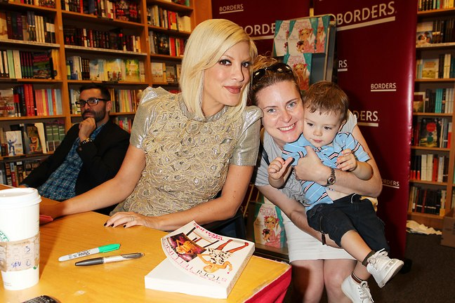 Tori Spelling, gold shimmer top, black leggings, book signing, borders, presenting tallulah
