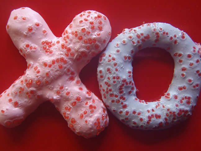 Meringue cookies shapes in to x and o's with red sugar on top
