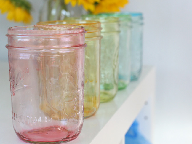 a rainbow of tinted mason jars on a white background