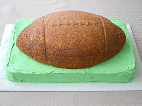 place the cake on top of the green icing football field