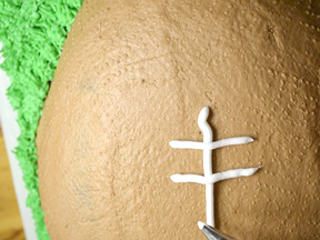 Piping the threading to the football cake
