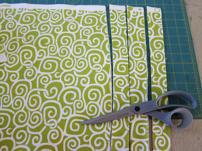 cutting the green spiral fabric in to strips with scissors
