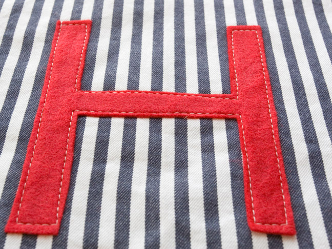 "a close up of the ""H"" sewn on to the white and blue pinstriped fabric"