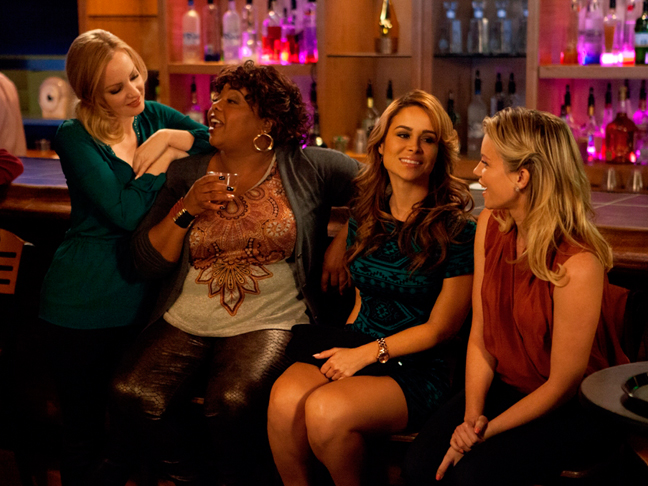a image from the single moms club movie four moms sit together laughing in jewel colored outfits at a bar
