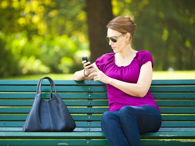 woman texting on park bench
