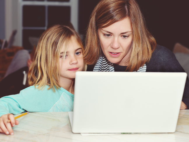mother looking at a white macbook laptop with her daughter