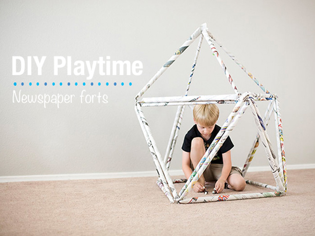 Child playing with a DIY newspaper fort