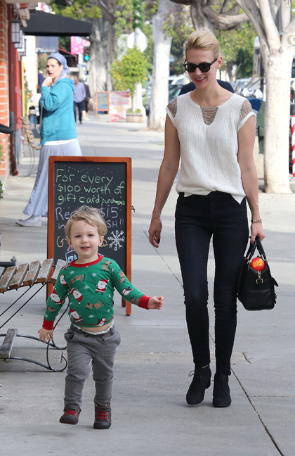 January Jones in a white blouse and sunglasses with her son