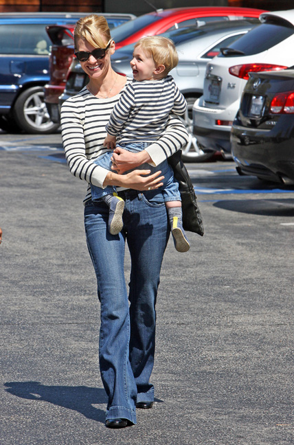 January Jones pictured holding her son in jeans and a striped shirt