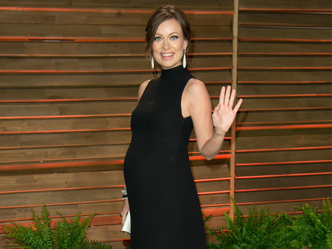 A pregnant Olivia Wilde in a form-fitting black turtleneck dress