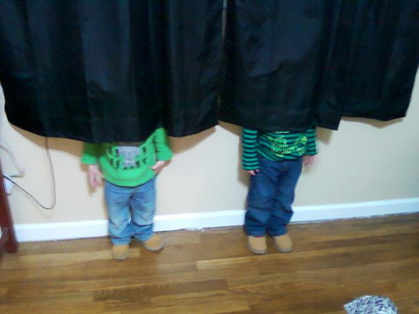 two boys playing hide and seek behind a curtain
