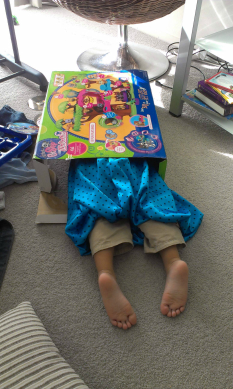child hiding in a toy box