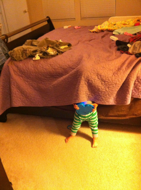 child hiding under a blanket holding toy