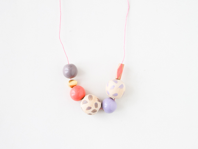 Beads strung up on pink cord for necklace.
