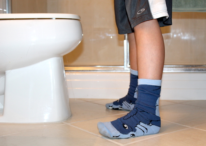 boy standing in front of toilet