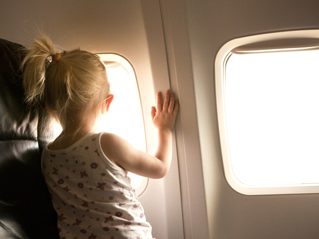 Toddler girl looking out airplane window in flight