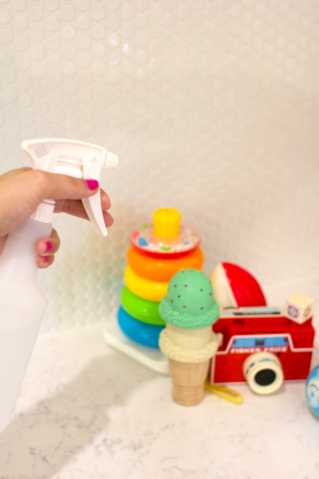 hand-spraying-nontoxic-cleaning-solution-on-toys