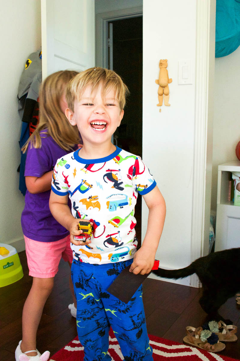 little boy laughing in his room with dinosaur pagamas