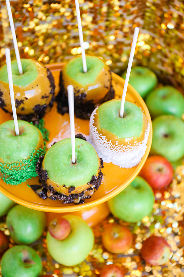 caramel apples dipped in candy on yellow cake stand