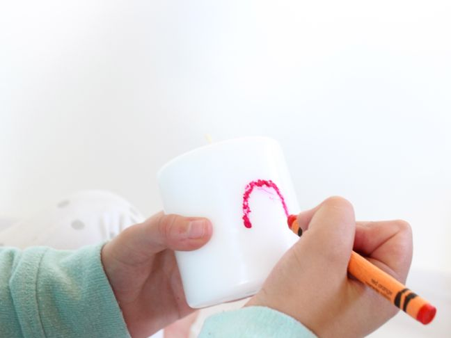 drawing heart with melted crayon on candle