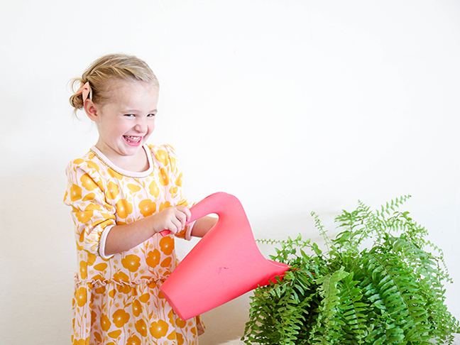little girl watering a plant
