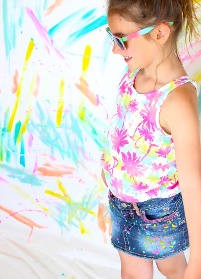 girl-wearing-a-bright-palm-tree-shirt-sunglasses-and-diy-paint-splatter-jeans