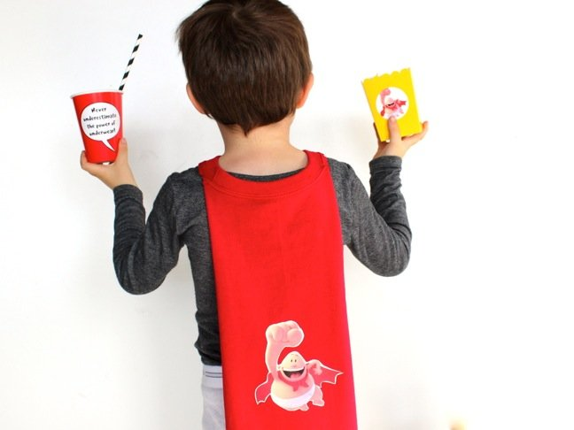 boy-wearing-a-captain-underpants-cape-and-holding-a-yellow-popcorn-box-and-red-cup