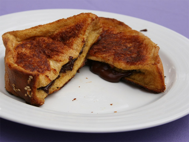 Two slices of Nutella baked french toast on a white plate with purple background