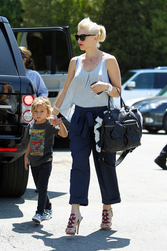 Gwen Stefani white tank top, blue pants cuffed, sunglasses, black bag, high heels
