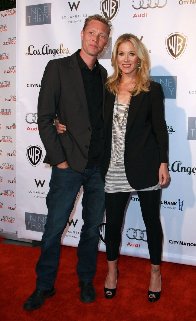 Christina Applegate black leggings, long necklace, black high heels, earrings, black blazer, printed blouse