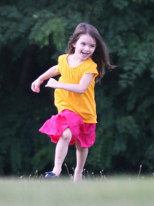 Suri Cruise, pink skirt, yellow top, running on lawn