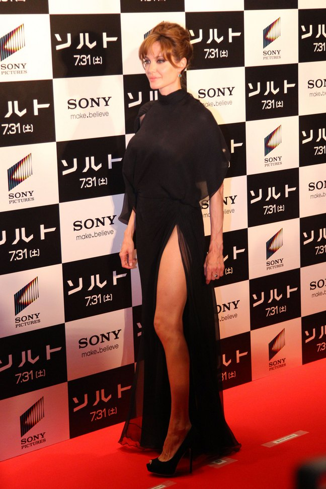 Angelina Jolie, black floor length dress slit to thigh, hair upswept, black peep toe high heels