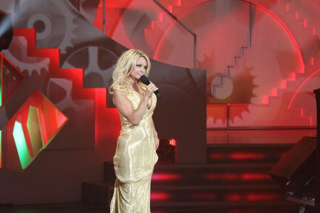 Pamela Anderson, gold dress, high heels, stage, montreal