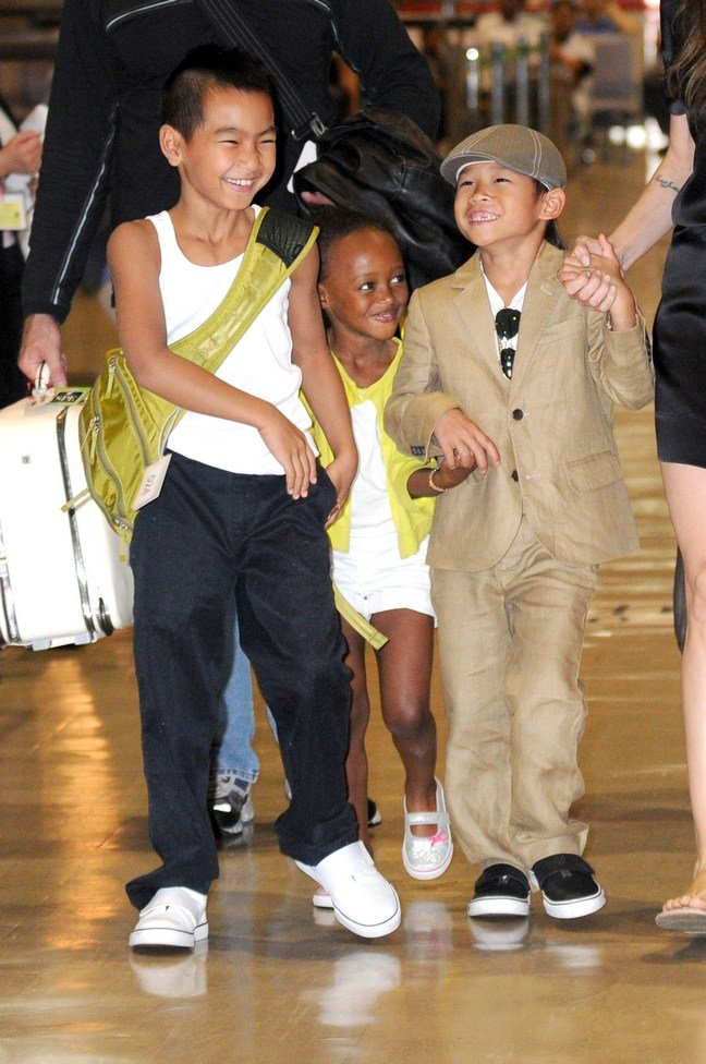 Maddox Jolie-Pitt, white tank top, black pants, green back pack, Pax Jolie-Pitt, beige suit