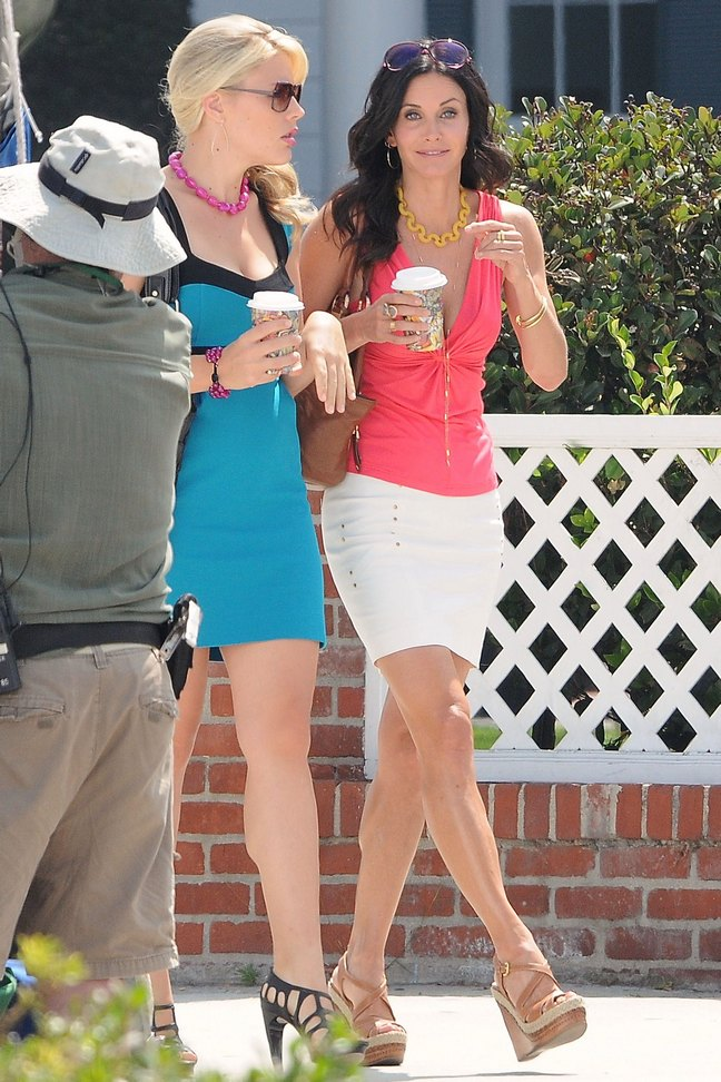 Courteney Cox, orange melon tank top blouse, white skirt, sunglasses, wedge sandals, coffee, Busy Philipps, blue dress, pink necklace, black strappy heels