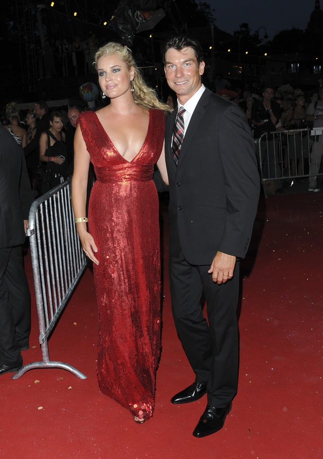 Rebecca Romijn, red shimmery floor-length dress, diamond bracelet, dangle earrings