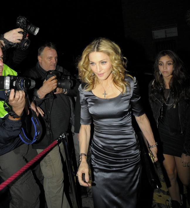 Madonna, silver gray form fitting dress, gray nylons, crucifix clutch, cross necklace, bracelets