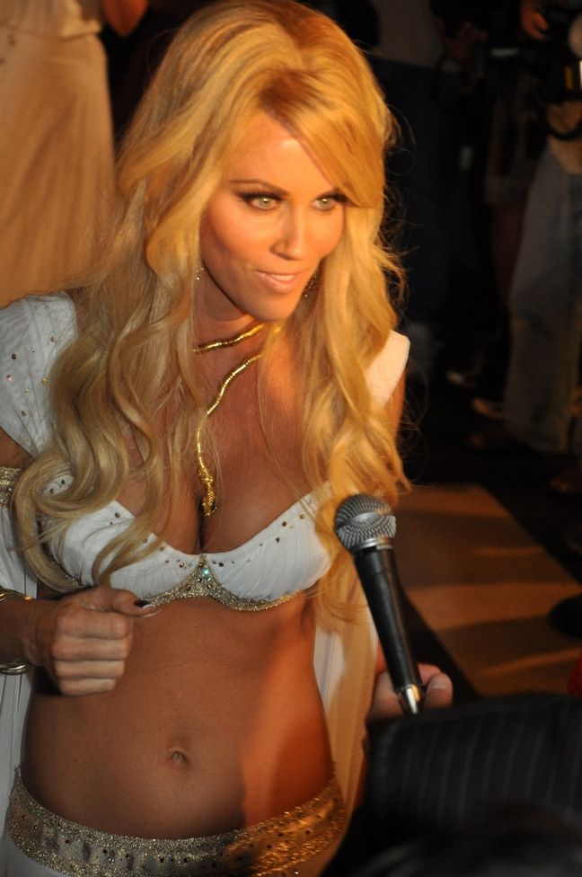 Jenny McCarthy, white bikini top, gold arm bands, bikini bottoms, snake necklace
