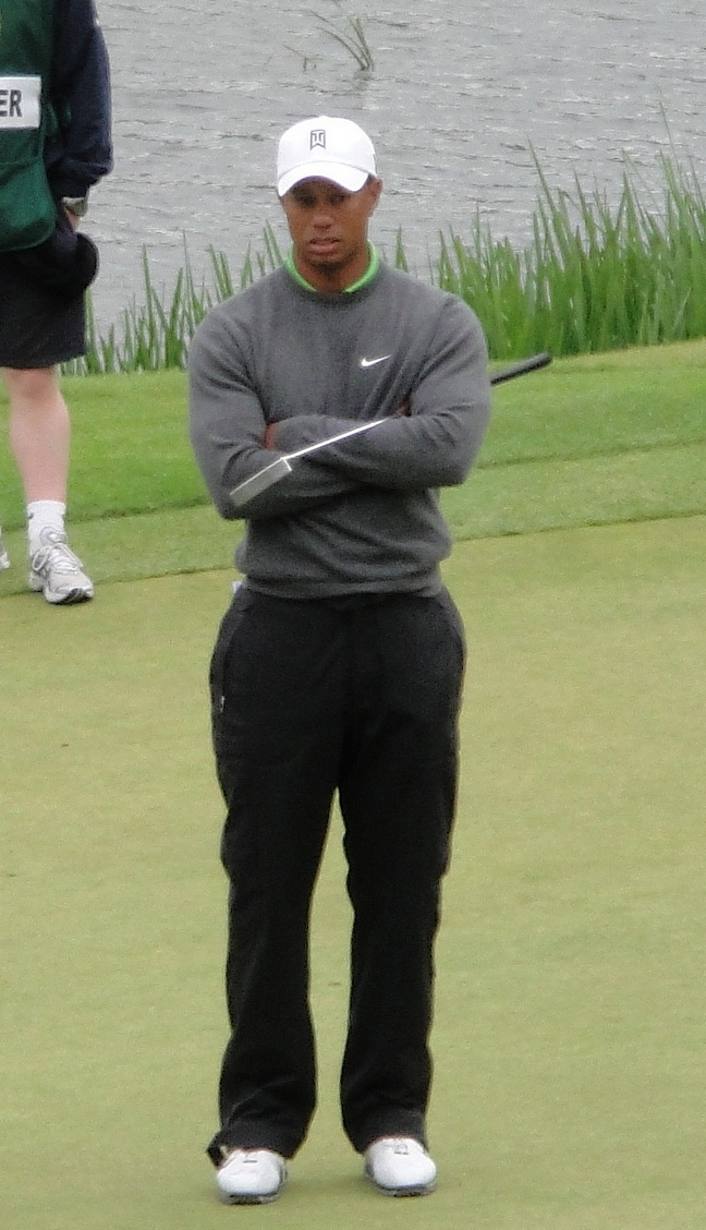 Tiger Woods, black pants, gray nike sweater, white golf shoes, white baseball hat