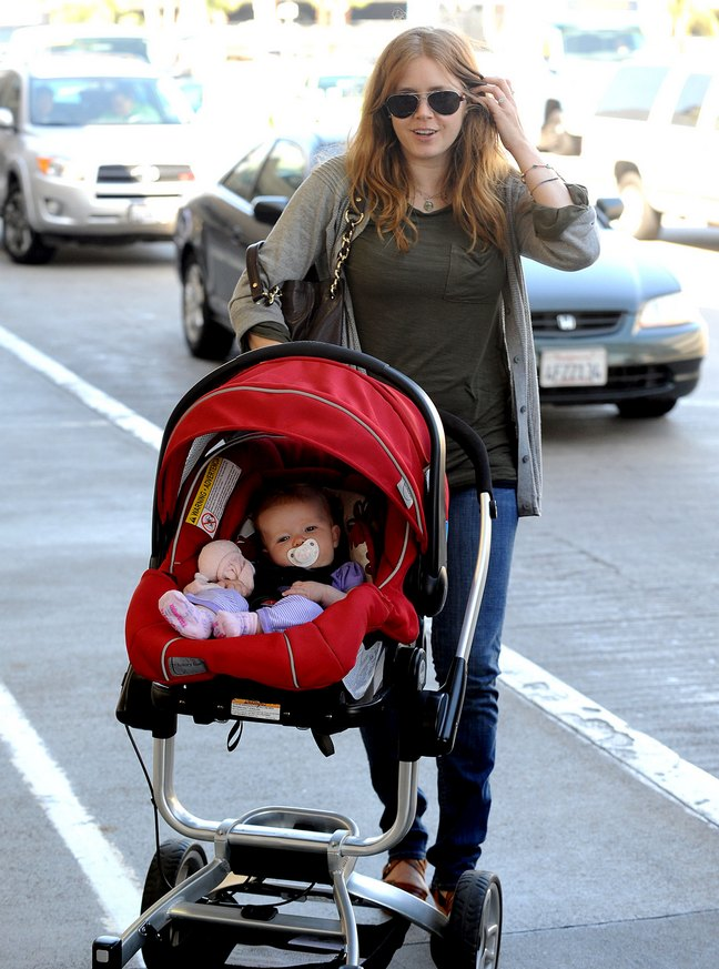Amy Adams, red baby carrier, red car seat, gray sweater, sunglasses, jeans, brown long sleeved shirt