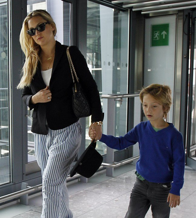 Kate Hudson, blue and white striped pants, black jacket, white shirt, sunglasses, black hat