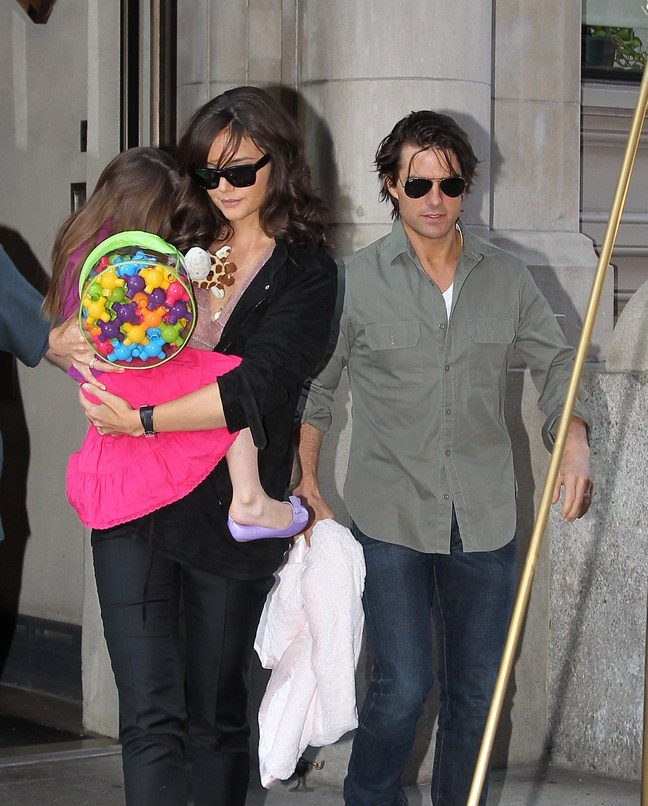 Tom Cruise, khaki shirt, sunglasses, jeans, Katie Holmes, black top, black pants, sunglasses, Suri Cruise, pink dress, colorful backpack