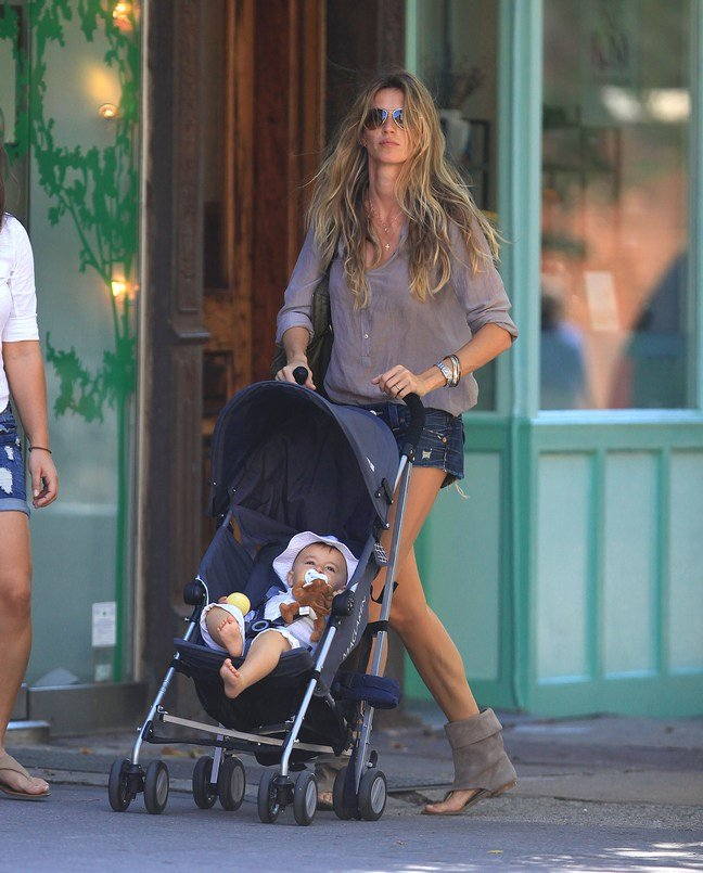 Gisele Bundchen, tan top, denim shorts, jean shorts, cutoff shorts, tan sandals, suede sandals, bracelets, sunglasses, tote bag, stroller