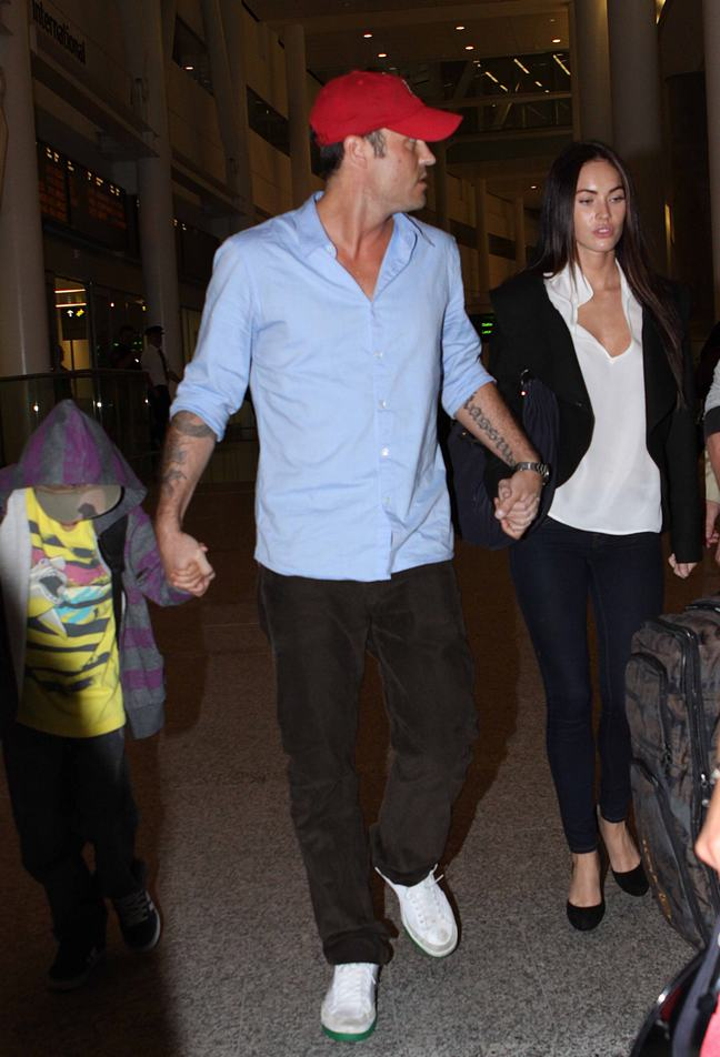 Brian Austin Green, light blue shirt, red baseball hat, black jeans, white shoes, Megan Fox, skinny jeans, white shirt, black ballet slippers, black jacket