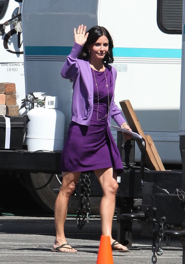 Courteney Cox, purple dress, purple jacket, long necklace, flip flops,