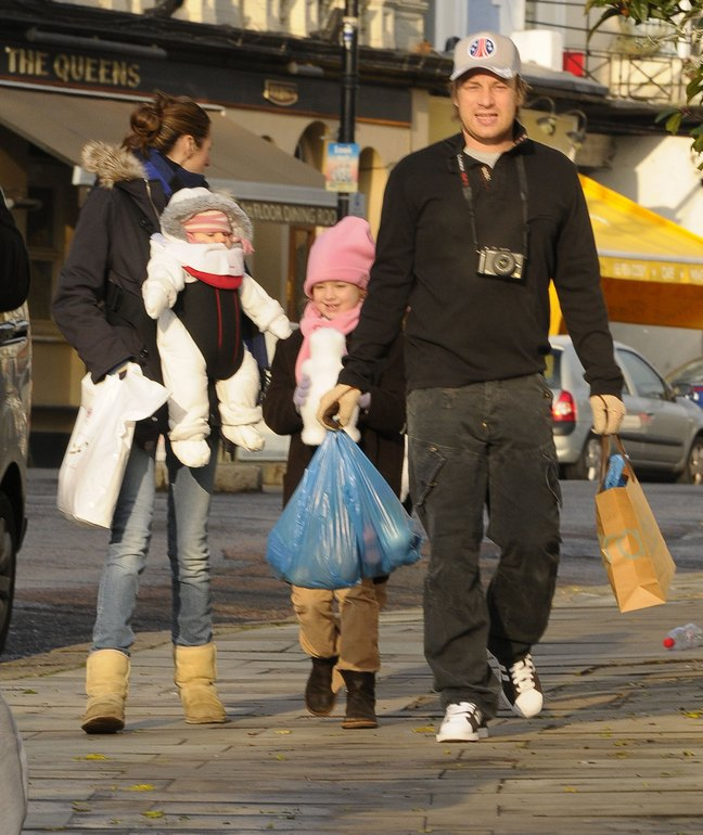 Jamie Oliver, black jacket, jeans, baseball hat, camera, athletic shoes, grocery bags