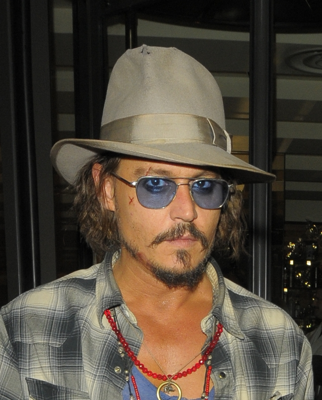 Johnny Depp, tan hat, blue tinted sunglasses, plaid shirt, blue tshirt, necklaces
