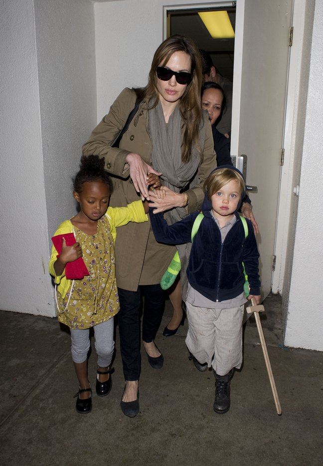 Angelina Jolie, brown trench coat, black ballet flats, black leggings, sunglasses, brown scarf, Shiloh, Zahara