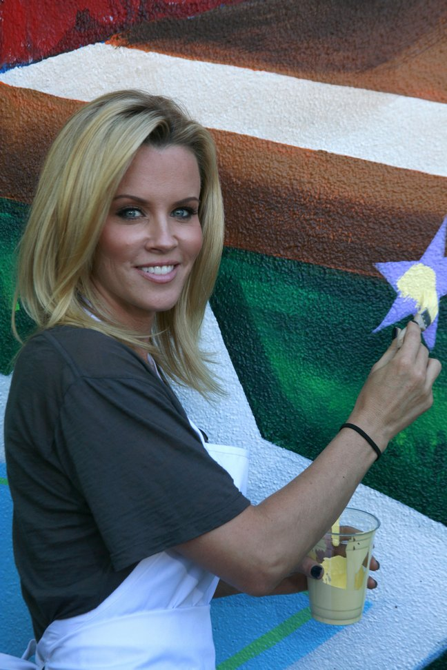 Jenny McCarthy, gray t-shirt, white apron, paintbrush, ponytail holder, black bracelet, paint cup