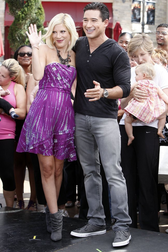 Tori Spelling, purple dress, strapless dress, large necklace, gray boots, Mario Lopez, black shirt,